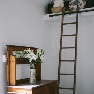 Esempio di un piccolo soggiorno country chiuso con pareti bianche, pavimento in ardesia e stufa a legna