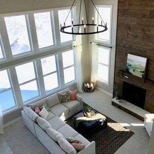 Immagine di un grande soggiorno country aperto con pareti grigie, moquette, camino classico, cornice del camino in legno e pavimento beige