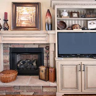 Diseño de sala de estar con biblioteca tradicional, pequeña, con paredes beige, chimenea tradicional, marco de chimenea de madera y pared multimedia