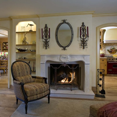 Example of a mid-sized ornate open concept light wood floor and brown floor family room design in Orange County with a standard fireplace, yellow walls, a media wall and a plaster fireplace