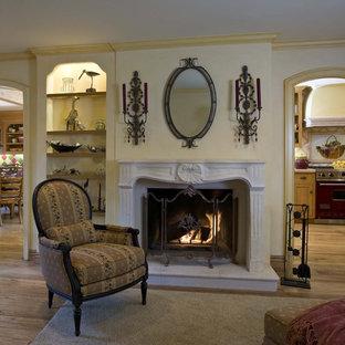 Cette image montre une salle de séjour victorienne de taille moyenne et ouverte avec une cheminée standard, un mur jaune, un sol en bois clair, un téléviseur encastré, un manteau de cheminée en plâtre et un sol marron.
