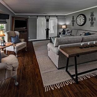 Foto di un soggiorno country di medie dimensioni e chiuso con pareti grigie, parquet scuro, nessun camino, porta TV ad angolo e pavimento marrone
