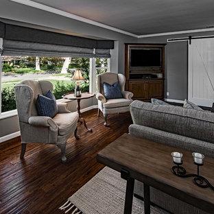 Esempio di un soggiorno country di medie dimensioni e chiuso con pareti grigie, parquet scuro, nessun camino, porta TV ad angolo e pavimento marrone
