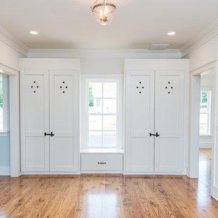Ejemplo de sala de estar abierta, de estilo de casa de campo, de tamaño medio, con suelo de madera en tonos medios, chimenea tradicional y marco de chimenea de ladrillo