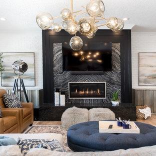 Inspiration för mellanstora klassiska avskilda allrum, med en hemmabar, vita väggar, ljust trägolv, en bred öppen spis, en spiselkrans i sten, en väggmonterad TV och brunt golv