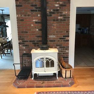 ボストンの大きいコンテンポラリースタイルのおしゃれなファミリールーム (ベージュの壁、淡色無垢フローリング、薪ストーブ、レンガの暖炉まわり) の写真