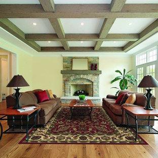Idee per un grande soggiorno chic aperto con pareti gialle, pavimento in legno massello medio, camino classico, cornice del camino in pietra, nessuna TV e pavimento marrone