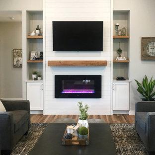 Großes, Offenes Country Wohnzimmer mit grauer Wandfarbe, dunklem Holzboden, Gaskamin, Kaminumrandung aus Holz, Wand-TV und braunem Boden in Sonstige