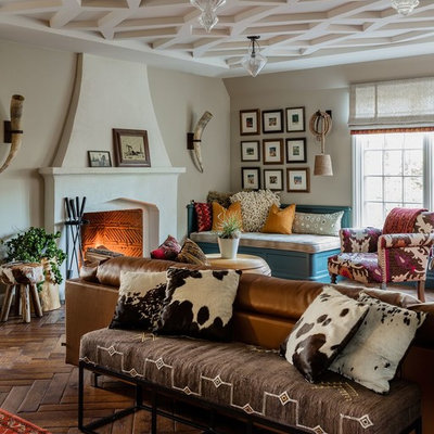 Eclectic medium tone wood floor and brown floor family room photo in Boston with beige walls and a standard fireplace