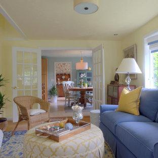 Immagine di un soggiorno costiero di medie dimensioni e stile loft con pareti gialle, pavimento in legno massello medio, camino classico, cornice del camino in cemento e nessuna TV