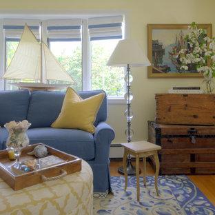 Idée de décoration pour une salle de séjour mansardée ou avec mezzanine marine de taille moyenne avec un mur jaune, un sol en bois brun, une cheminée standard, un manteau de cheminée en béton et aucun téléviseur.