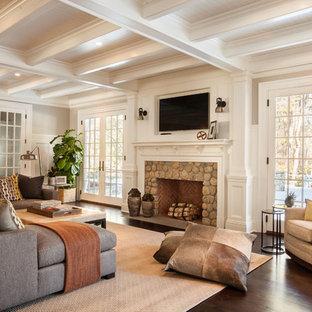 Modelo de sala de estar cerrada, clásica, de tamaño medio, con paredes beige, suelo de madera oscura, chimenea tradicional, marco de chimenea de piedra y televisor colgado en la pared