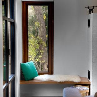 アデレードの小さいコンテンポラリースタイルのおしゃれなファミリールーム (白い壁、コンクリートの床、薪ストーブ、レンガの暖炉まわり) の写真