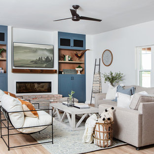 Mid-sized cottage open concept porcelain tile and beige floor family room photo in Phoenix with white walls, a ribbon fireplace, a plaster fireplace and a wall-mounted tv