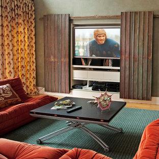 Idée de décoration pour une grande salle de séjour bohème avec un téléviseur dissimulé, un mur vert, un sol en bois clair, aucune cheminée et un sol orange.