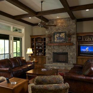 Cette photo montre une salle de séjour craftsman avec un mur beige, un sol en bois foncé, une cheminée standard, un manteau de cheminée en pierre et un téléviseur encastré.