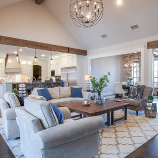This is an example of a large country open concept family room in Dallas with grey walls, dark hardwood floors, a wall-mounted tv and brown floor.