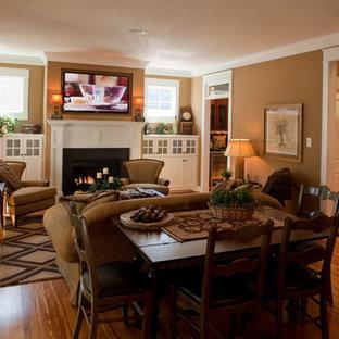 Foto di un soggiorno american style di medie dimensioni e chiuso con pareti beige, pavimento in legno massello medio, camino classico, cornice del camino in metallo e TV a parete