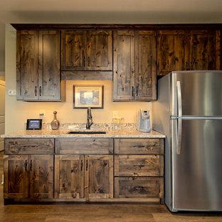 アトランタの大きいおしゃれな独立型ファミリールーム (ホームバー、ベージュの壁、ラミネートの床、標準型暖炉、石材の暖炉まわり、壁掛け型テレビ、茶色い床) の写真
