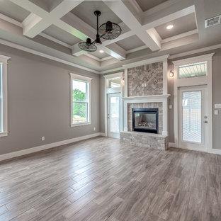 他の地域の大きいおしゃれなファミリールーム (ホームバー、グレーの壁、磁器タイルの床、両方向型暖炉、レンガの暖炉まわり、壁掛け型テレビ、茶色い床) の写真