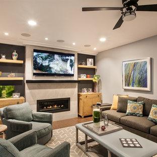 Modelo de sala de estar abierta, clásica renovada, pequeña, con paredes grises, suelo de madera oscura, chimenea lineal, marco de chimenea de baldosas y/o azulejos y televisor colgado en la pared