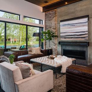 ボイシの中サイズのインダストリアルスタイルのおしゃれなファミリールーム (マルチカラーの壁、横長型暖炉、コンクリートの暖炉まわり、テレビなし、黒い床) の写真