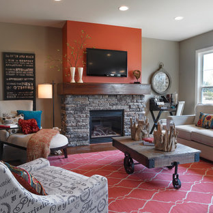 Aménagement d'une salle de séjour classique ouverte et de taille moyenne avec un manteau de cheminée en pierre, un téléviseur fixé au mur, un mur orange, une cheminée standard, un sol en bois foncé et un sol marron.