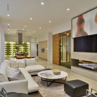 Diseño de sala de estar abierta, contemporánea, con paredes blancas, chimenea de doble cara y televisor colgado en la pared