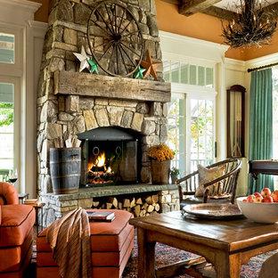 Cette photo montre une salle de séjour chic avec un mur orange et un manteau de cheminée en pierre.
