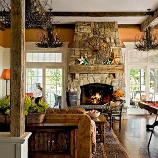 Imagen de sala de juegos en casa tradicional con parades naranjas y marco de chimenea de piedra