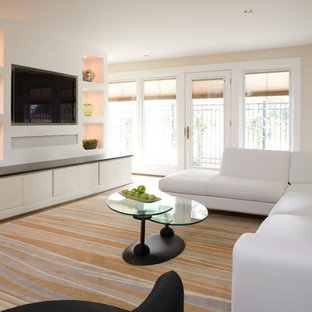 Example of a trendy family room design in DC Metro with beige walls and a media wall