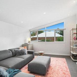 シドニーの中サイズのミッドセンチュリースタイルのおしゃれなファミリールーム (白い壁、カーペット敷き、横長型暖炉、漆喰の暖炉まわり、壁掛け型テレビ、グレーの床) の写真