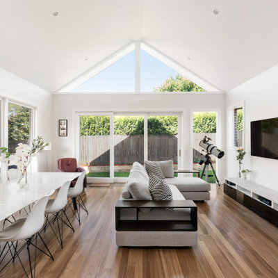 Inspiration for a mid-sized contemporary open concept family room remodel in Sydney with white walls and a wall-mounted tv