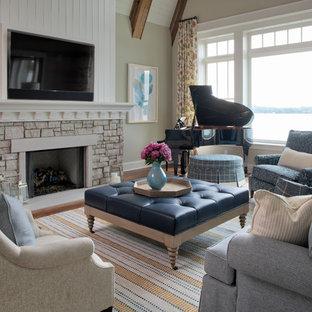 ミネアポリスの中サイズのビーチスタイルのおしゃれな独立型ファミリールーム (ミュージックルーム、ベージュの壁、無垢フローリング、標準型暖炉、石材の暖炉まわり、壁掛け型テレビ、茶色い床) の写真