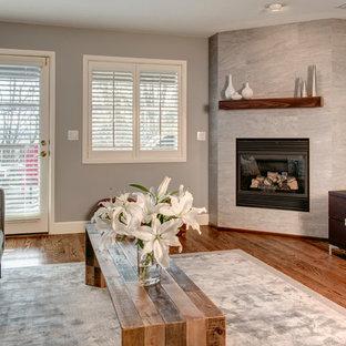 シアトルの中サイズのコンテンポラリースタイルのおしゃれなファミリールーム (グレーの壁、無垢フローリング、コーナー設置型暖炉、タイルの暖炉まわり、据え置き型テレビ) の写真