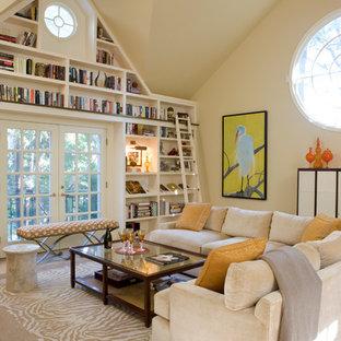 Foto di un grande soggiorno classico stile loft con libreria, pareti beige, pavimento in laminato, pavimento beige, camino classico, cornice del camino in pietra e TV a parete