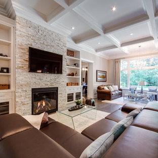 トロントの大きいトラディショナルスタイルのおしゃれなファミリールーム (石材の暖炉まわり、ベージュの壁、無垢フローリング、標準型暖炉、壁掛け型テレビ、茶色い床) の写真