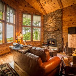シャーロットの中サイズのラスティックスタイルのおしゃれなファミリールーム (茶色い壁、無垢フローリング、標準型暖炉、石材の暖炉まわり、壁掛け型テレビ、茶色い床) の写真