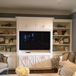 Foto di un piccolo soggiorno classico chiuso con libreria, pareti grigie, pavimento in legno massello medio, nessun camino e parete attrezzata