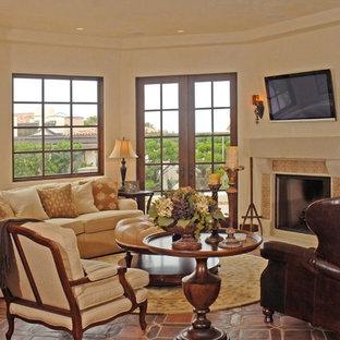 サンディエゴの中サイズの地中海スタイルのおしゃれなファミリールーム (ベージュの壁、テラコッタタイルの床、標準型暖炉、タイルの暖炉まわり、壁掛け型テレビ、ゲームルーム、茶色い床) の写真