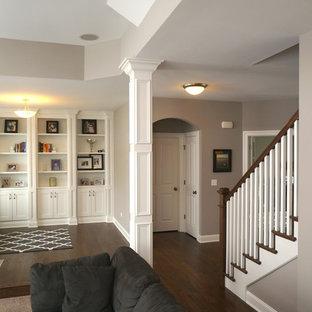 Exemple d'une grande salle de séjour avec une bibliothèque ou un coin lecture craftsman ouverte avec un mur gris, moquette et un téléviseur encastré.