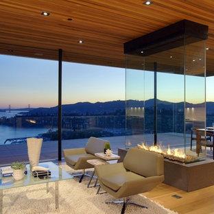 Modelo de sala de estar abierta, contemporánea, extra grande, con paredes beige, suelo de piedra caliza, chimenea de doble cara y marco de chimenea de piedra