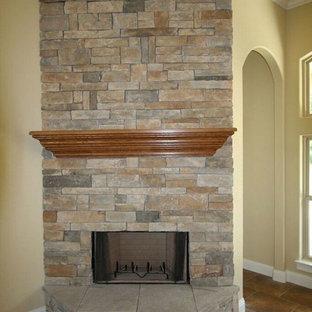 他の地域の小さいトラディショナルスタイルのおしゃれなオープンリビング (ベージュの壁、磁器タイルの床、コーナー設置型暖炉、石材の暖炉まわり、茶色い床) の写真