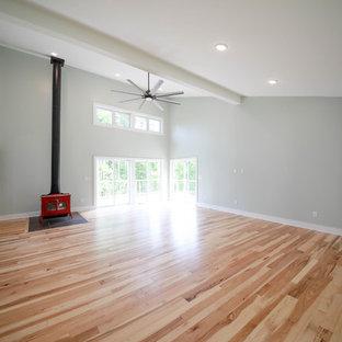 他の地域のコンテンポラリースタイルのおしゃれなファミリールーム (青い壁、無垢フローリング、薪ストーブ、タイルの暖炉まわり、茶色い床) の写真