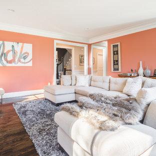 Cette image montre une salle de séjour traditionnelle de taille moyenne et fermée avec un mur orange, un sol en bois foncé, une cheminée standard, un manteau de cheminée en béton, un téléviseur fixé au mur et un sol marron.