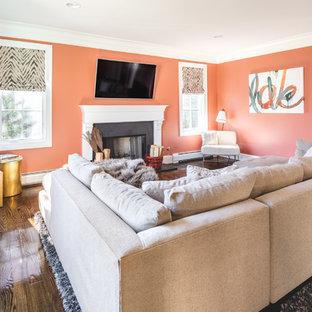 Exemple d'une salle de séjour chic de taille moyenne et fermée avec un mur orange, un sol en bois foncé, une cheminée standard, un manteau de cheminée en béton, un téléviseur fixé au mur et un sol marron.