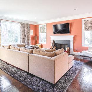 Réalisation d'une salle de séjour tradition de taille moyenne et fermée avec un mur orange, un sol en bois foncé, une cheminée standard, un manteau de cheminée en béton, un téléviseur fixé au mur et un sol marron.