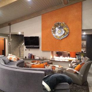 Immagine di un grande soggiorno minimal aperto con pareti arancioni, pavimento con piastrelle in ceramica, camino ad angolo, cornice del camino in pietra, TV a parete, pavimento grigio, soffitto a volta e pannellatura