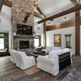 Foto di un soggiorno country con pareti bianche, TV a parete, camino classico, cornice del camino in mattoni e pavimento multicolore