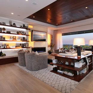 Modern inredning av ett stort allrum med öppen planlösning, med vita väggar, ljust trägolv, en bred öppen spis, en väggmonterad TV, beiget golv och en spiselkrans i metall